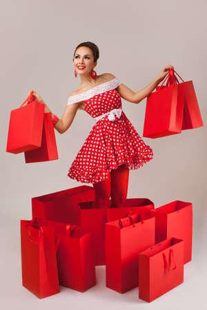 Grappig portret van een glimlachend leuk jong vrouwelijk model die vele het winkelen zakken in haar wapens houden die rode kleding dragen