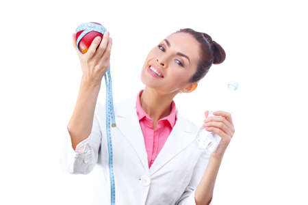 Cheerful woman holding apple with a tape measure on it and  bottle of water. Selective focus, isolated on white background. photo