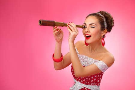 De vrouw kijkt door een telescoop en het maken van een verbaasde uitdrukking. Zij bevindt zich tegen een roze achtergrond. Stockfoto