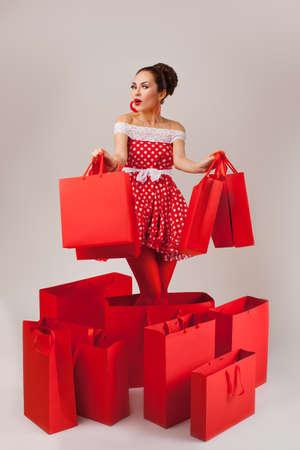 Grappig portret van een verrast schattige jonge vrouwelijke model bedrijf veel boodschappentassen in haar armen dragen rode jurk Stockfoto