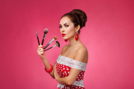 makeover: Beauty Girl with Makeup Brushes. Natural Make-up for Brunette Woman. Beautiful Face. Makeover. Perfect Skin. Pin-Up Retro style.