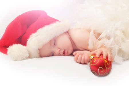 De baby van de Kerstman rode hoed en houdt decoratie van de kerstboom