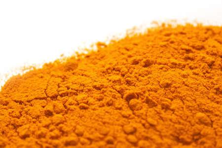 tumeric: Tumeric spilt across a white background. Orange color.