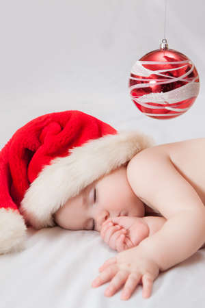 Sleeping baby Santa Claus red hat and  Christmas tree decoration photo