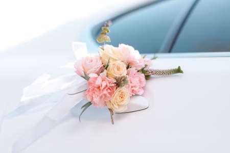 Bruiloft auto met mooie decoraties van roze en oranje rozen