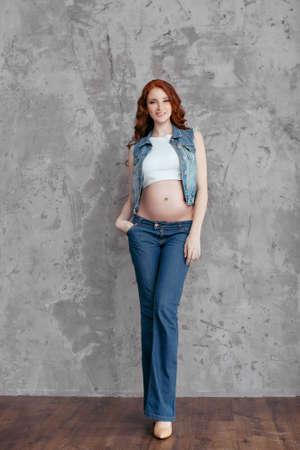 sexy pregnant woman: Studio portrait of beautiful slim sexy pregnant woman wearing casual jeans over grunge gray wall