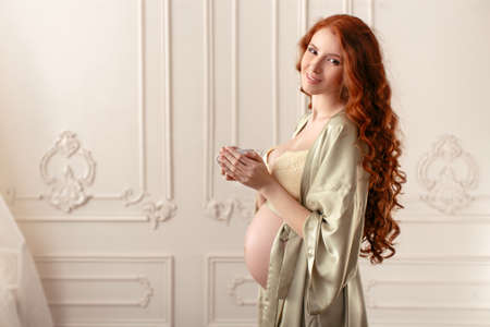 Portret van een vrij jong meisje dat en kop thee glimlacht houdt Stockfoto