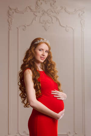 Pregnant girl with red curls standing in a crown and a red dress Stock Photo