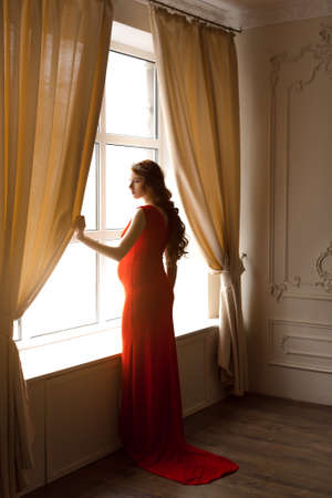 Pregnant girl with red curls standing in red dress and looks in window