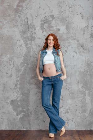 sexy pregnant woman: グランジの灰色の壁を越えてカジュアルなジーンズを着て美しいスリムなセクシーな妊娠中の女性のスタジオ ポートレート