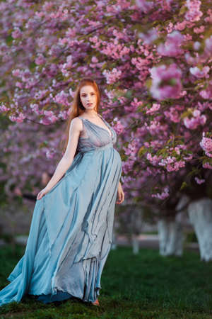 Beautiful pregnant woman standing among trees, outdoor in nature.