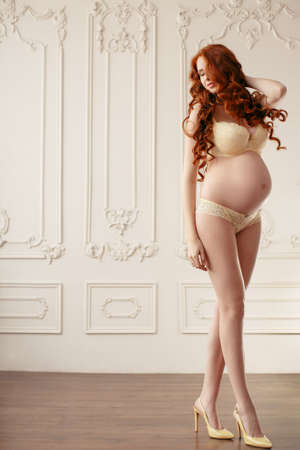 Slim beautiful pregnant model posing at home. Beautiful lingerie. Stylish and sexy pregnancy.