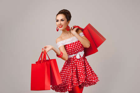 modelo: Retrato divertido de un modelo joven linda sonrisa femenina que sostiene muchos bolsos de compras en sus brazos llevaba vestido rojo Foto de archivo