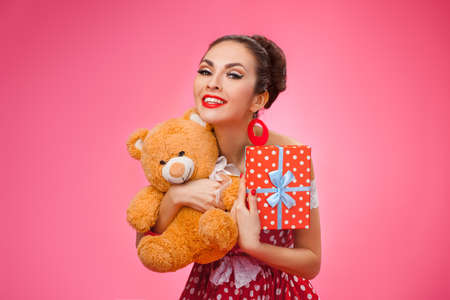 teddy bear love: Funny portrait of a smiling cute young female model embraces gift box and toy bear. Pink Background