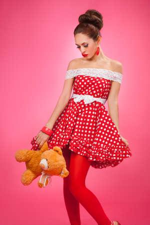 mujer decepcionada: Mujer decepcionada regalo oso de peluche, con un vestido retro rojo