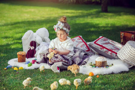 conceived: Cute little baby girl in park on green grass. Poster for Easter holiday. Selective focus on child Stock Photo