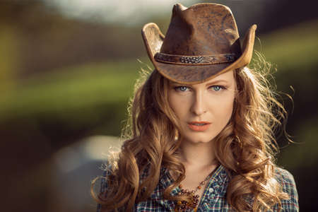 Portrait of young cowgirl outdoors. Retro style model