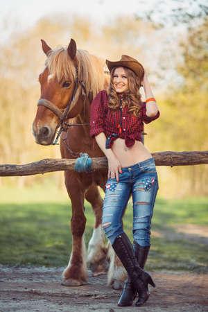 Cowgirl joven y caballo al aire libre. Sexy modelo de moda