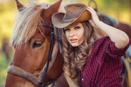 horses in field: Portrait of young smiling cowgirl and horse outdoors