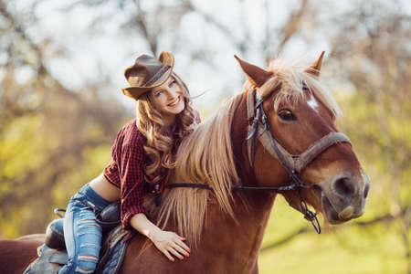 Beautiful young brunette woman on a horseback 写真素材