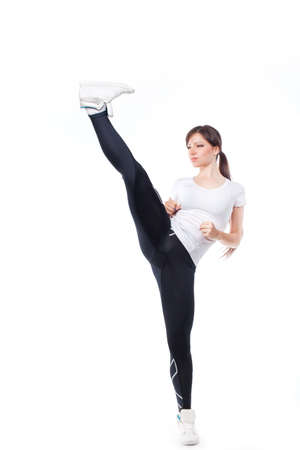 female boxing: Woman practicing tae-bo exercises, kicking forward with legs. Photo set of sporty female brunette girl wearing sports clothes over white background Stock Photo