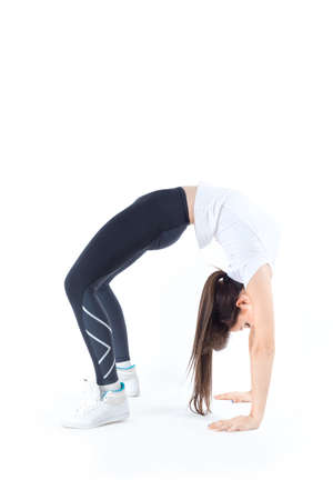 ductile: Ductile flexible beautiful young woman makes athletic, gymnastic exercises in crab position isolated on white background