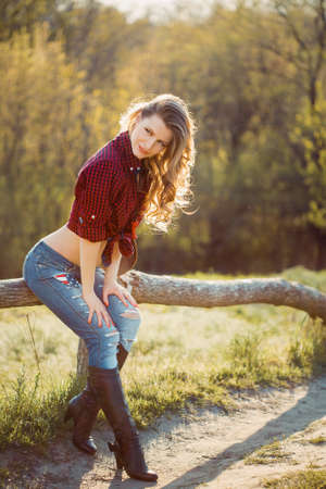 Young Cowgirl Outdoors. Sexy Fashion Model Posing in Nature Stock Photo