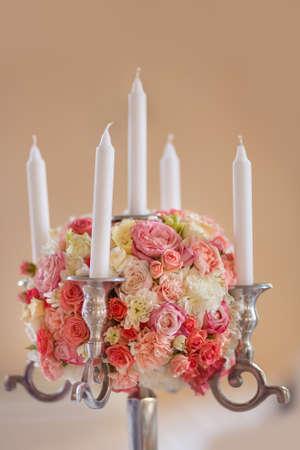 Centrepiece: Candlestick. Wedding reception centerpiece close-up with pastel orange and white.