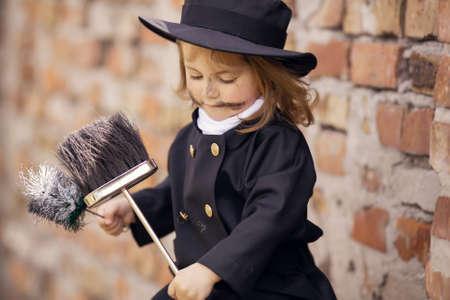 Chica como un deshollinador contra la pared de ladrillo. Foto de archivo - 55638235