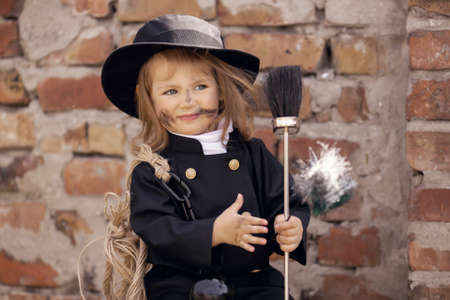 sweep: Girl as a chimney sweep against brick wall.