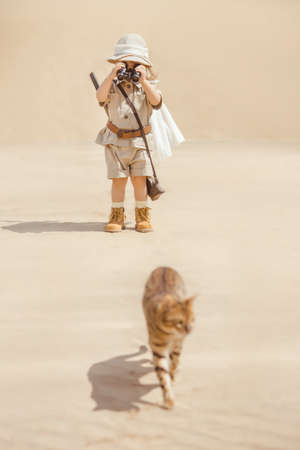 seeker: Concept of travel and fascinating adventures. hild in suit of treasures seeker like Indiana Jones in the desert whit wild cat similar to tiger Stock Photo