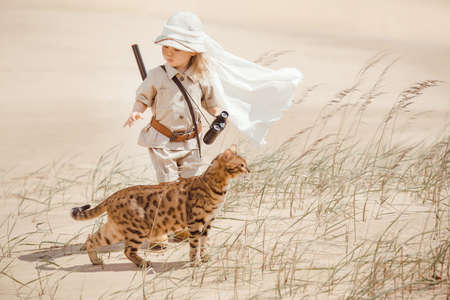 Concept of travel and fascinating adventures. hild in suit of treasures seeker like Indiana Jones in the desert whit wild cat similar to tiger Archivio Fotografico