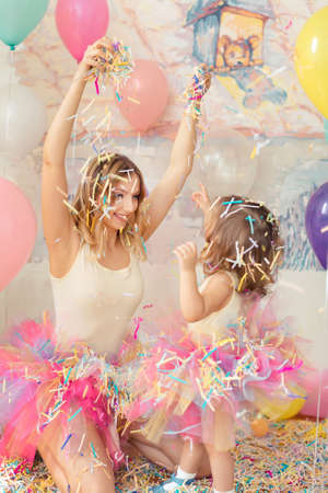 Mother day concept. Happy woman and young girl celebrate birthday plaing confetti.