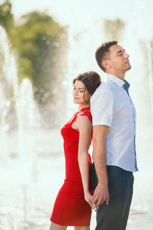 blindly: Young couple stand back to back with closed eyes and dream of their future life