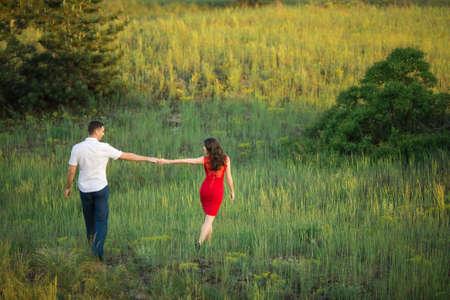 baiser amoureux: L'homme avec une fille sur la nature tenant les mains et marcher loin. Des relations
