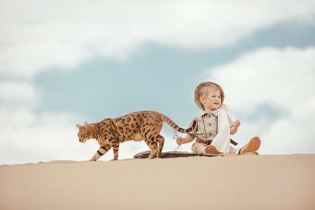 cinematic: Concept of travel and fascinating adventures. hild in suit of treasures seeker like Indiana Jones in the desert whit wild cat similar to tiger Stock Photo