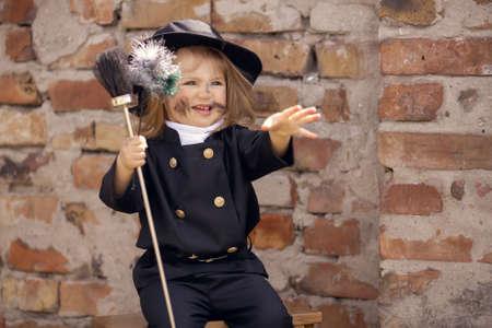 Meisje als schoorsteenveger tegen bakstenen muur.