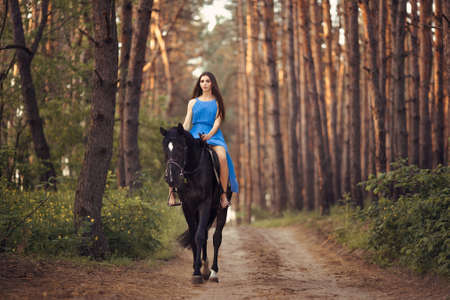 Young beautiful brunette girl in blue dress ride on the black horse in forest 스톡 콘텐츠