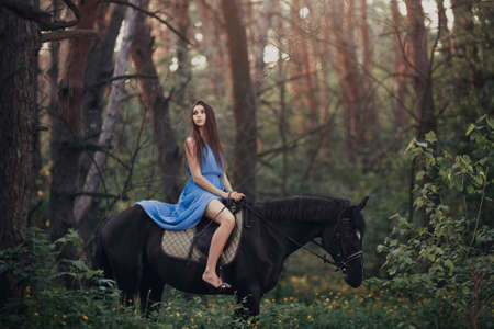 Young beautiful brunette girl in blue dress ride on the black horse in forest Reklamní fotografie