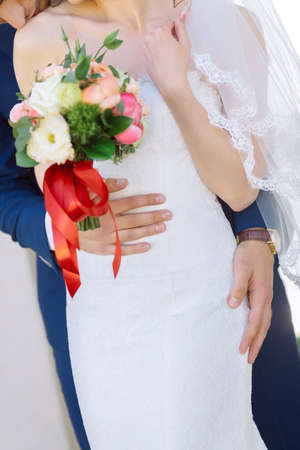 frill: Wedding. The groom in a suit hugs bride in a white dress