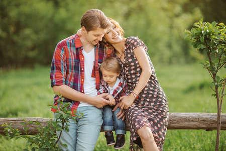 Happy Family op de natuur. Moeder vader en zoon in casual kleding, zitten op een hek, landelijke uitstraling, buitenshuis