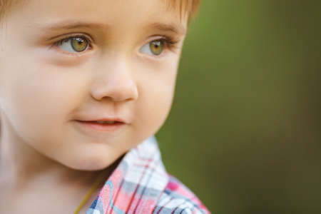 niños rubios: Cute little boy playing outdoor on the nature. Close-up portrait