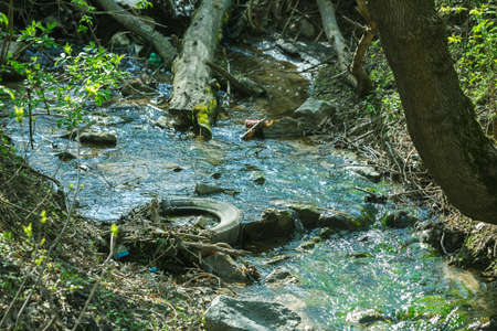 Garbage in spring steam. Tainted water resources, water pollution idea