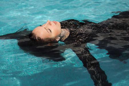 Portrait of the beautiful woman in black dress floating in blue water