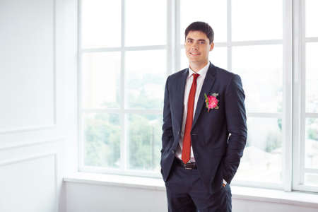 man in suite: Gorgeous smiling groom looking at camera. Handsome man in a suite with a buttonhole standing against a window indoors
