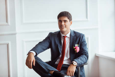 man in suite: Gorgeous smiling groom looking at camera. Handsome man in a suite with a buttonhole sitting on chair against white wall indoors