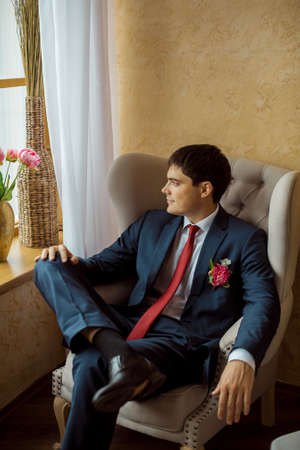 buttonhole: Gorgeous smiling groom. Handsome man in a suite with a buttonhole sitting on chair and looking in window indoors