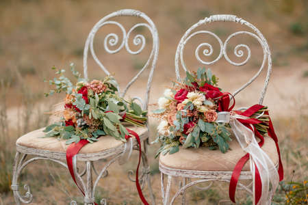 Beautiful wedding colorful bouquets for bride on retro chairs in forest. Beauty of colored flowers. Bridal accessories. Female decoration for girl. Details for marriage and for married couple Stock Photo