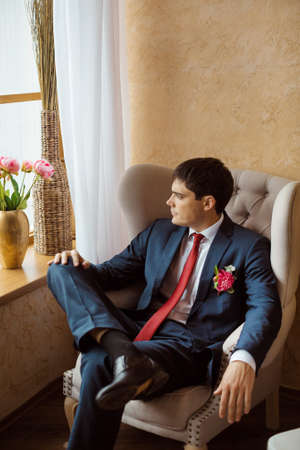 man in suite: Gorgeous serious groom. Handsome man in a suite with a buttonhole sitting on chair and looking in window indoors Stock Photo