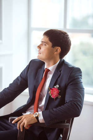 man in suite: Gorgeous serious groom. Handsome man in a suite with a buttonhole sitting on chair against white wall indoors